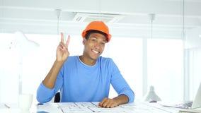 Overwinningsteken door Afro-Amerikaanse architecturale ingenieur op het werk