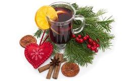 Overwogen die wijn in glas met pijpje kaneel, Kerstmisboom en hart op een wit wordt geïsoleerd Stock Foto's
