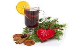 Overwogen die wijn in glas met pijpje kaneel, Kerstmisboom en hart op een wit wordt geïsoleerd Stock Foto