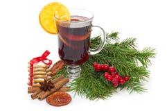 Overwogen die wijn in glas met pijpje kaneel, Kerstmisboom en suikergoed op een wit wordt geïsoleerd Stock Foto's