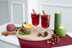 Overwogen die wijn met kruiden in glas en sinaasappelen op smaak wordt gebracht stock foto's