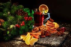 overwogen die wijn op Kerstmislijst met noten, mandarijnen, kaneel, Kerstboomtakken wordt verfraaid, royalty-vrije stock afbeelding