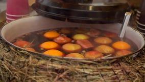 Overwogen wijn in een steelpan met appelen en sinaasappelen Hete Drank Fruitdrank De Markt van het voedsel Straatvoedsel stock videobeelden