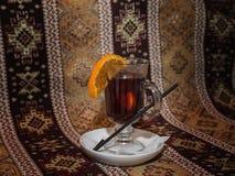 Overwogen wijn in glasmok met oranje plak Stock Foto's