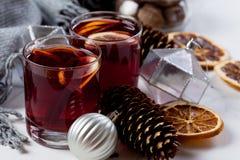 Overwogen wijn in glazen met sinaasappel en kruiden met grijze sjaal royalty-vrije stock afbeeldingen