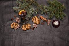 Overwogen wijn met geurige kruiden op een donkere leerachtergrond met chocoladeschilferkoekjes een tak van een Kerstboom en een N royalty-vrije stock afbeeldingen