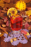 Overwogen wijn, sinaasappelen, noten en snoepjes op achtergrond de herfstbladeren Stock Foto