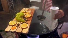 Overwogen wijn in steelpan Hete Drank Fruitdrank De Markt van het voedsel Het eten van snel voedsel Straatvoedsel stock footage