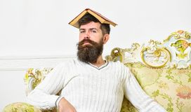 Overwork concept. Macho sits with open book on head, like roof. Guy, teacher overdid with teaching, became crazy. Professor. Man with beard and mustache sits on stock photography