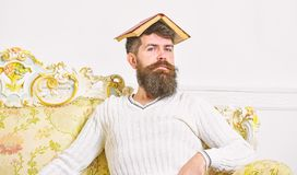 Overwork concept. Macho sits with open book on head, like roof. Guy, teacher overdid with teaching, became crazy. Professor. Man with beard and mustache sits on royalty free stock photo