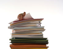 Overworked. Hand reaches for a report on top of a pile of paperwork Royalty Free Stock Photography