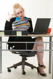 Overworked. Blond business woman sitting at desk pointing fingers at head while looking at an overflowing in box of files showing too much work Stock Images