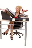 Overworked. Blond woman secretary sitting at desk with over flowing in box with a person handing more work with a overwhelmed expression Royalty Free Stock Photos