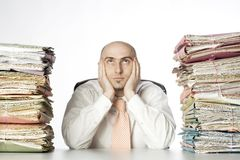 Overworked administrator. A view of an office worker sitting at a desk or table, holding his head in his hands, overwhelmed by two huge piles of paperwork and Stock Image