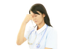 Overworked Asian female nurse Stock Image