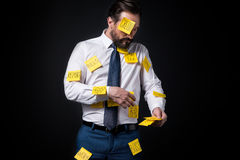 Overworked bearded businessman with sticky notes on clothes standing Stock Images
