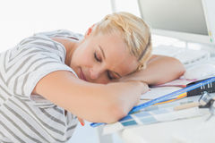 Overworked blonde designer napping on her desk Royalty Free Stock Photography