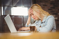 Overworked blonde sitting and using laptop Stock Images