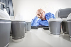 Overworked and bored businessman at office. Exhausted and overworked office worker. Man drinks too much coffee Stock Image