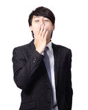 Overworked business man yawning. With black rim of eye isolated on white background, model is a asian people Royalty Free Stock Images