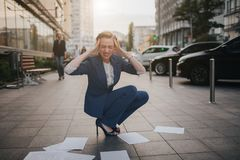 Overworked business woman having a lot of paperwork. Business woman surrounded by lots of papers. Business woman. Standing in the heap of papers royalty free stock image