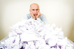 Overworked businessman. Overworked bald headed male businessman partially buried in paperwork; studio background Stock Photo