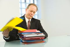 Overworked businessman. Portrait of busy senior businessman sat at desk with pile of paperwork Royalty Free Stock Photos