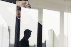 Overworked businessman with arm raised leaning on the other side of a glass wall Royalty Free Stock Image