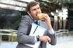 Overworked businessman eating fast food on the go.  Stock Images