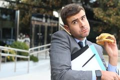 Overworked businessman eating fast food on the go.  Royalty Free Stock Images