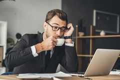 Overworked businessman in eyeglasses drinking coffee. At workplace Royalty Free Stock Photography