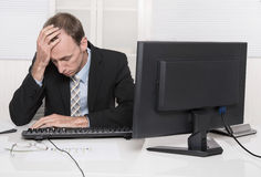 Overworked businessman frustrated and stressed in his office wit Stock Images