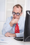 Overworked businessman with glasses staring into space at desk -. Stress and burnout - everyday life at the office Stock Photography