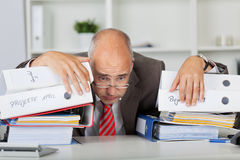 Overworked Businessman Leaning On Stack Of Binders. Overworked mature businessman leaning on stack of binders at desk in office Royalty Free Stock Photography