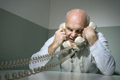 Overworked businessman on the phone Royalty Free Stock Photos