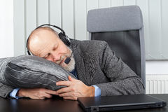 Overworked businessman. Picture of an overworked businessman sleeping at the office Stock Image