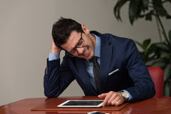Overworked Businessman Sitting By His Desk Royalty Free Stock Photos
