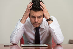 Overworked Businessman Sitting By His Desk Royalty Free Stock Photography