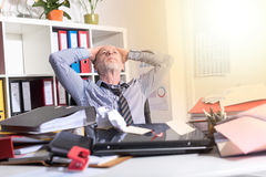 Overworked businessman sitting at a messy desk, light effect Stock Photos