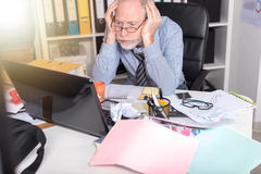Overworked businessman sitting at a messy desk, light effect Royalty Free Stock Photo