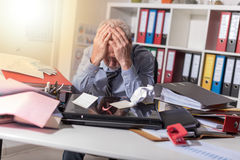 Overworked businessman sitting at a messy desk, light effect Stock Photography