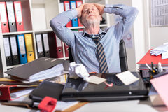 Overworked businessman sitting at a messy desk Stock Photography