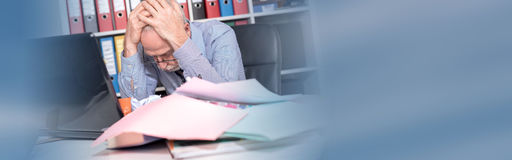 Overworked businessman sitting at a messy desk. In office Stock Images