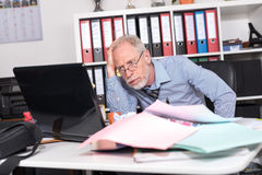 Overworked businessman sitting at a messy desk Royalty Free Stock Photos