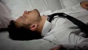 Overworked businessman sleeping on bed in suit, tiring busy work, lifestyle royalty free stock photos