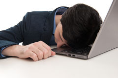 Overworked businessman sleeping on his laptop Royalty Free Stock Photos