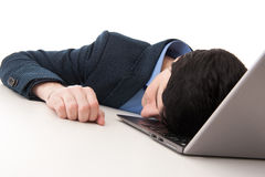 Overworked businessman sleeping on his laptop Stock Photos