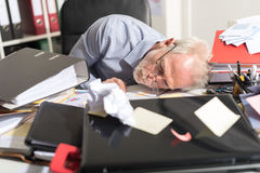 Overworked businessman sleeping on a messy desk Royalty Free Stock Photos