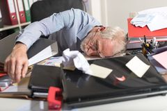 Overworked businessman sleeping on a messy desk. In office Stock Photos