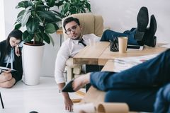 Overworked businessman sleeping at office with feet. On table Royalty Free Stock Images